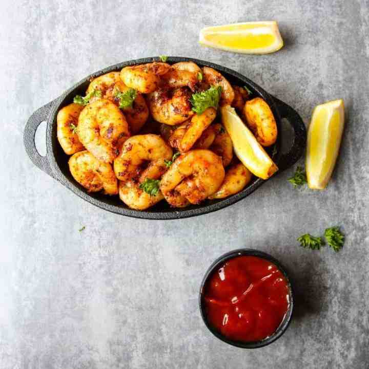 Shrimp in a pan on a table with lemon and sauce