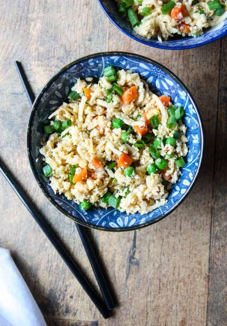 Cauliflower rice in a blue and white bowl with black chopsticks