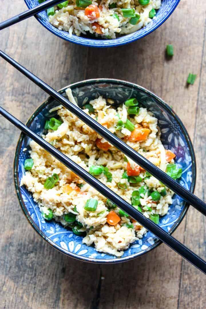 A bowl of food with rice and vegetables, with chopsticks