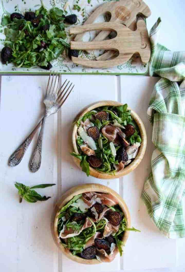 Two wooden bowls of fig salad beside a half empty salad platter