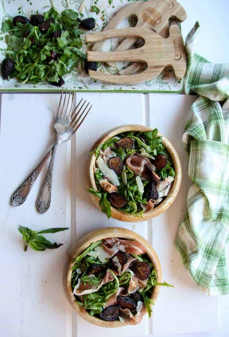 Two wooden bowls of fig salad beside a half empty salad platter