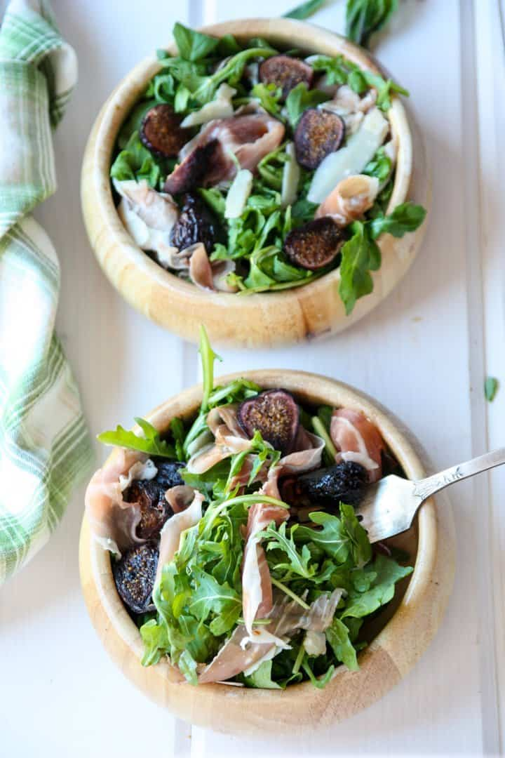 A bowl of salad on a plate, with Arugula