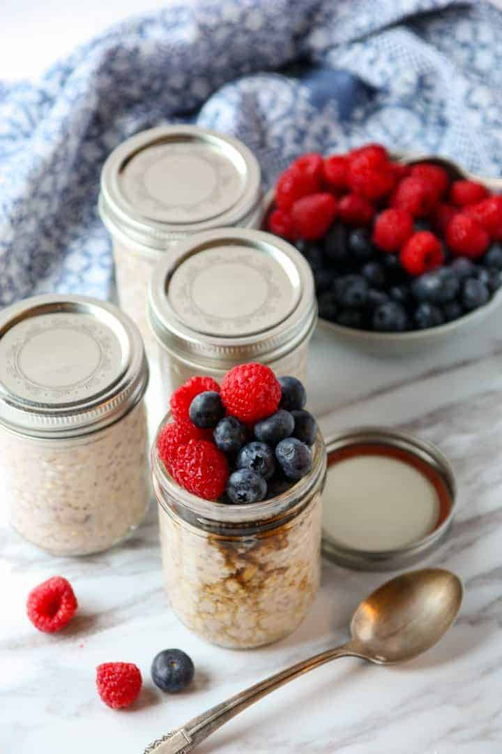 Jars of oatmeal and a bowl of berries
