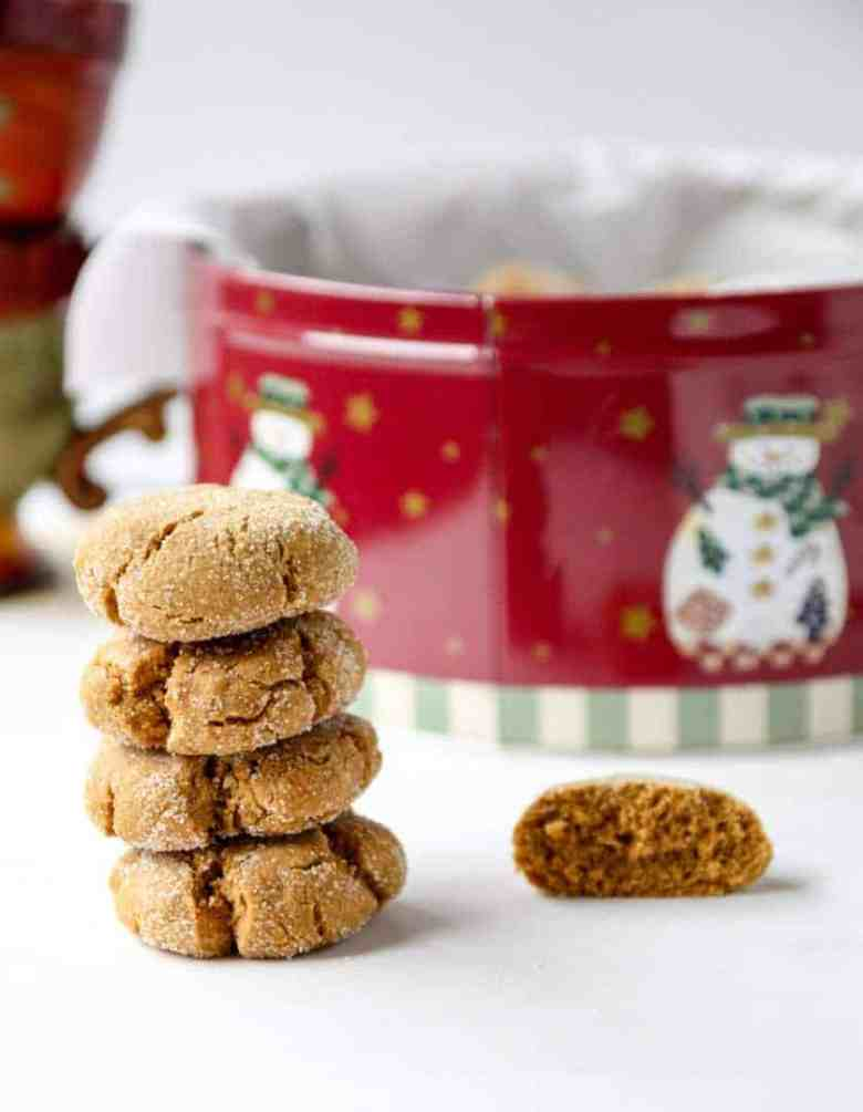 Stack of four ginger cookies in front of a red cookie tin.