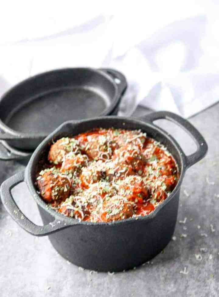 Top shot of meatless mushroom meatballs in marinara sauce, topped with parmesan cheese in black pot