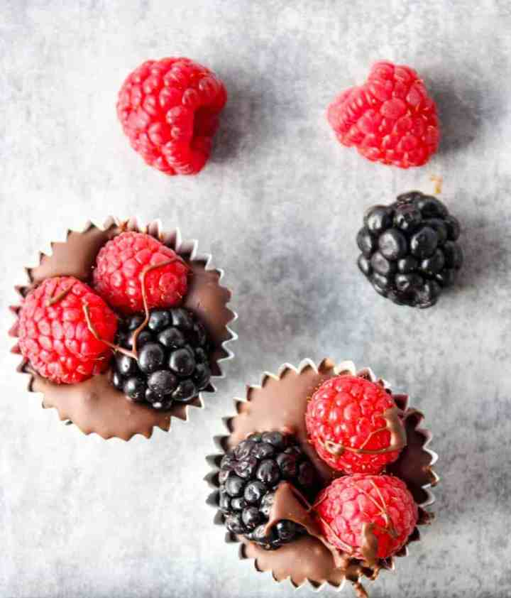 Close up top down shot of two homemade chocolate berry cups with raspberries and blackberries