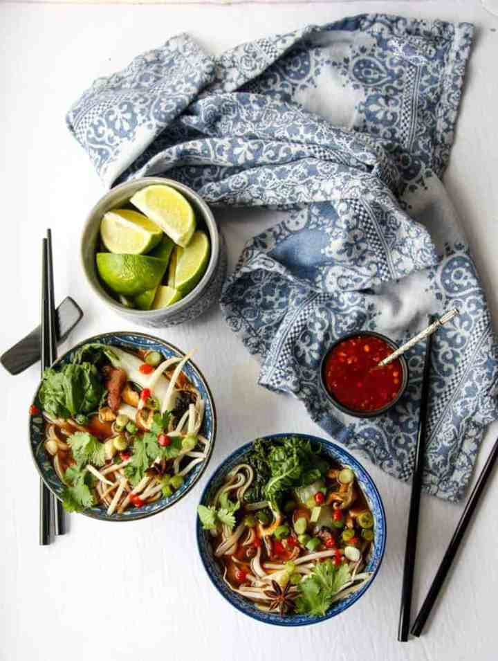 top shot of pho in two bowls next to black chopsticks, a bowl of lemon wedges, and a blue kitchen towel
