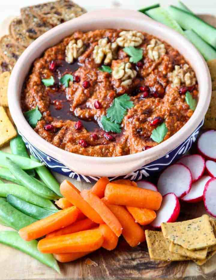 Muhammara dip in a clay bowl with dipping vegetables and crackers