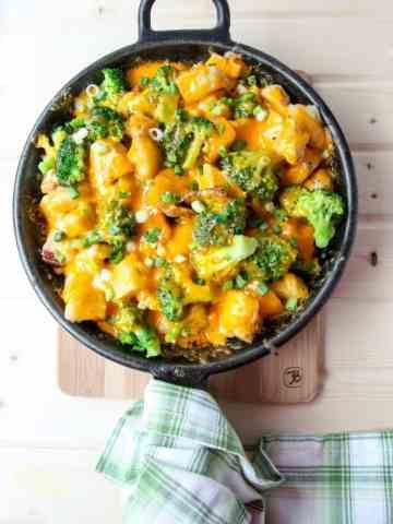 Cheese, broccoli, and potato casserole in black skillet.