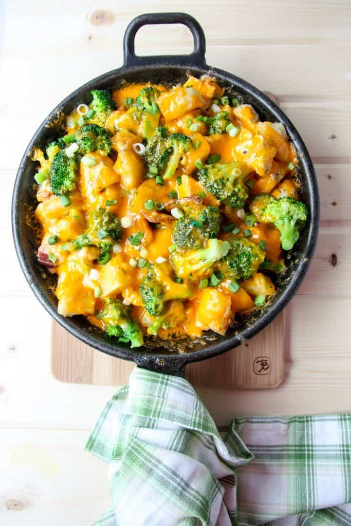 Ranch Chicken & Potato Casserole with broccoli & bacon covered in melted cheese in a cast iron skillet