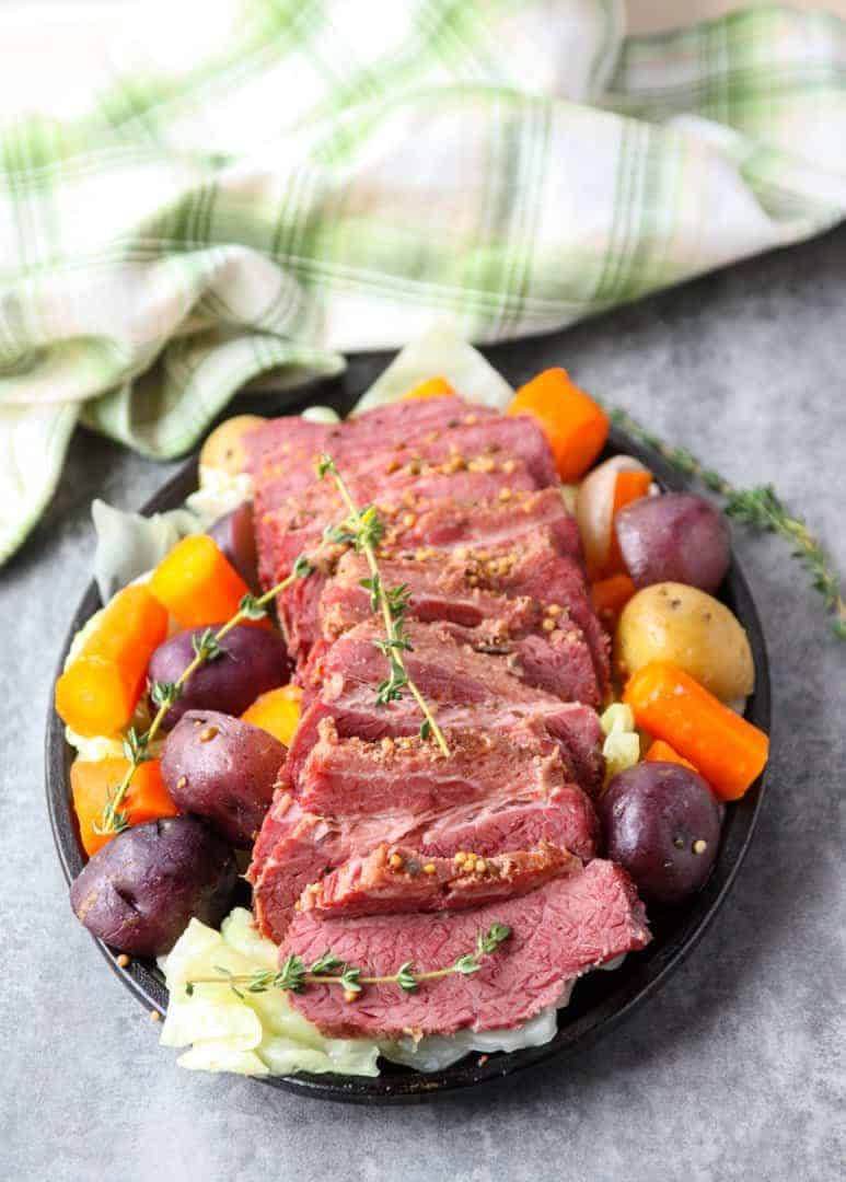 sliced slow cooker corned beef and cabbage with carrots and potatoes on a black cast iron pan.