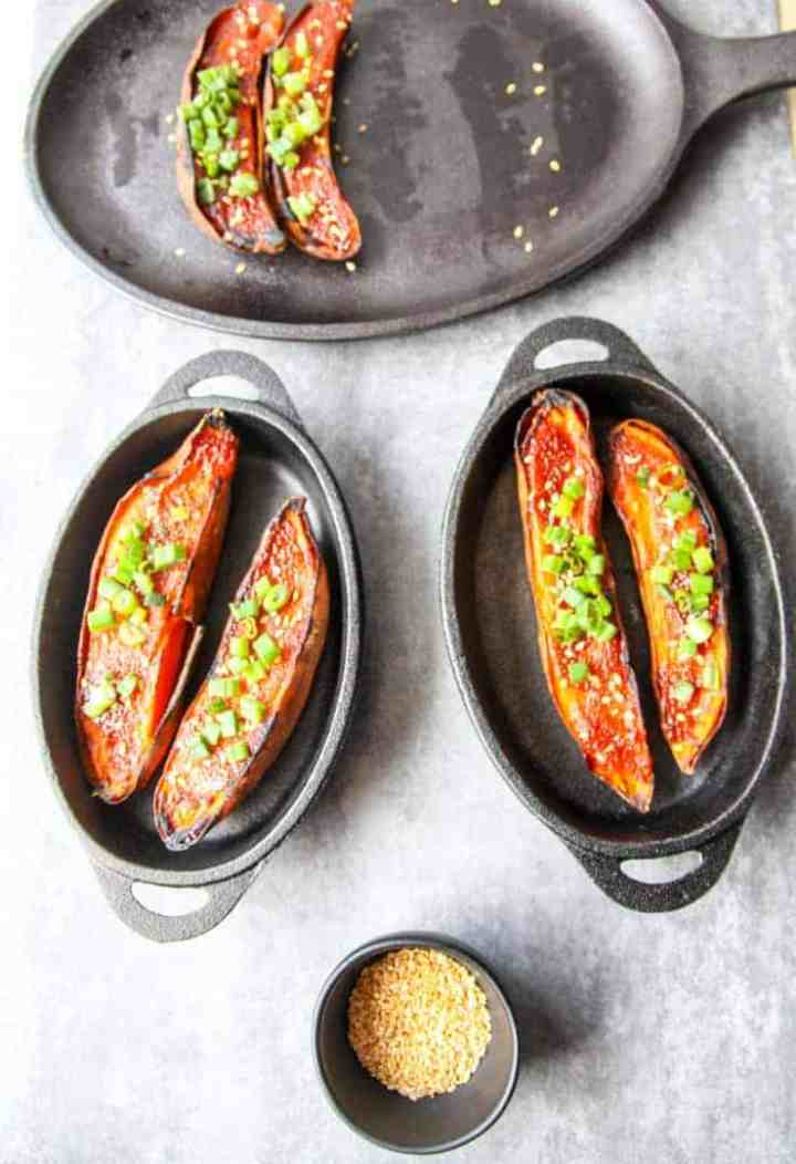Two cast iron serving dishes, each with two halves of miso baked sweet potatoes
