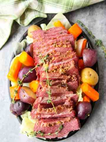 A round black plate of vegetables and sliced meat,