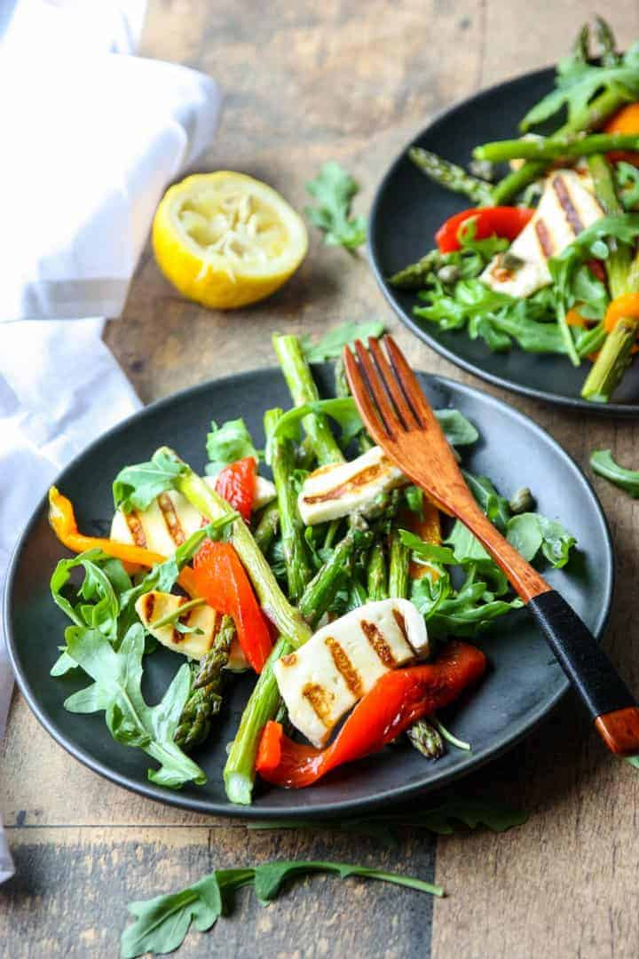 two black plates with roasted asparagus & pepper salad