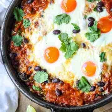 A skillet with eggs, black beans, sauce, and fresh cilantro in black skillet.