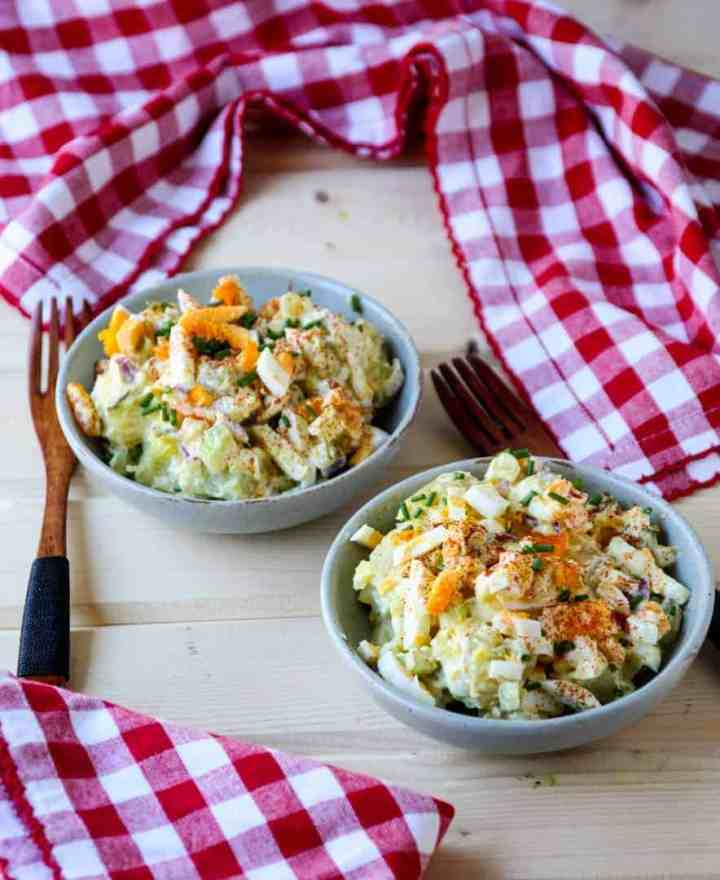 Two bowls of potato salad with red and white checkered napkins