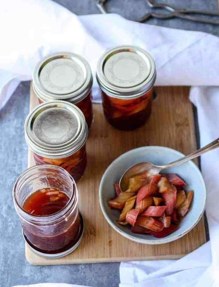 four jars of pickled rhubarb, on opened, and a dish of pickled rhubarb