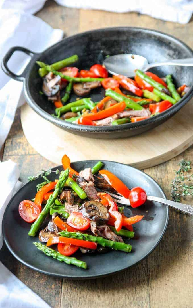 Cast ron pan with steak & asparagus stir fry and one serving of stir fry on a black plate