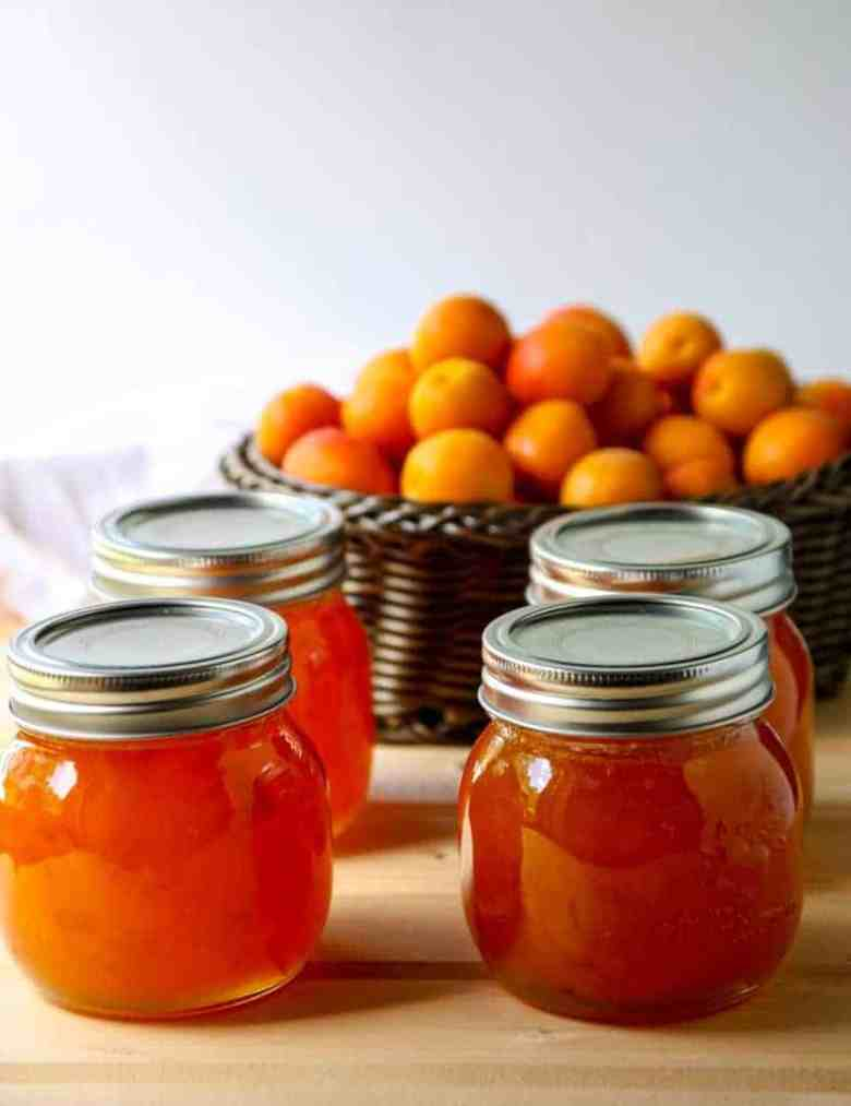 Four jars of jam with apricots in a basket