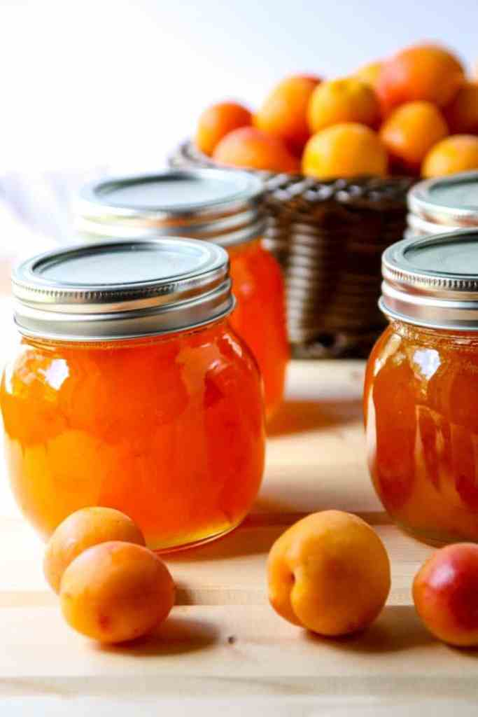 Four jars of apricot jam and a basket of fresh apricots