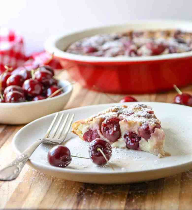 A slice of Cherry Almond Clafoutis on a white plate with a fork