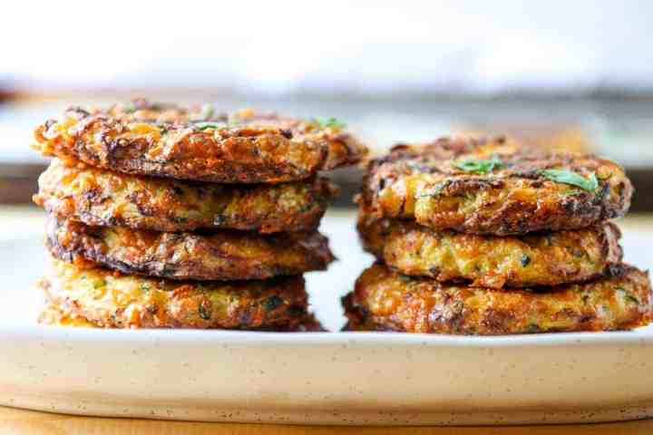 Two stacks of baked zucchini fritters on a plate