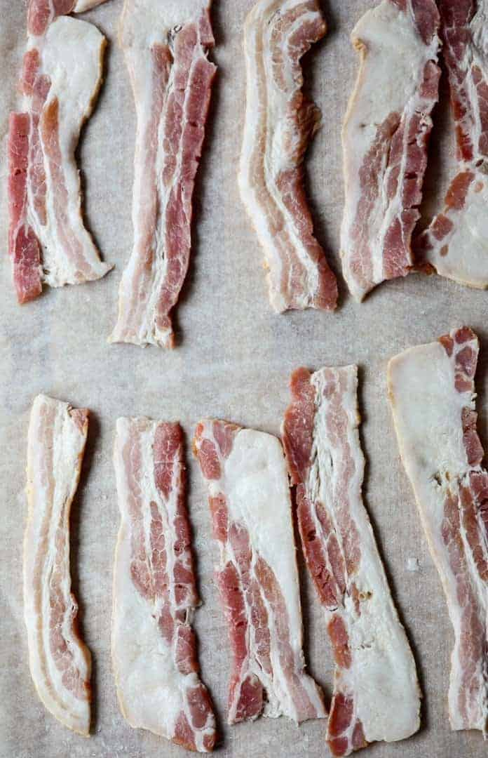 Ten strips of raw bacon on a baking sheet