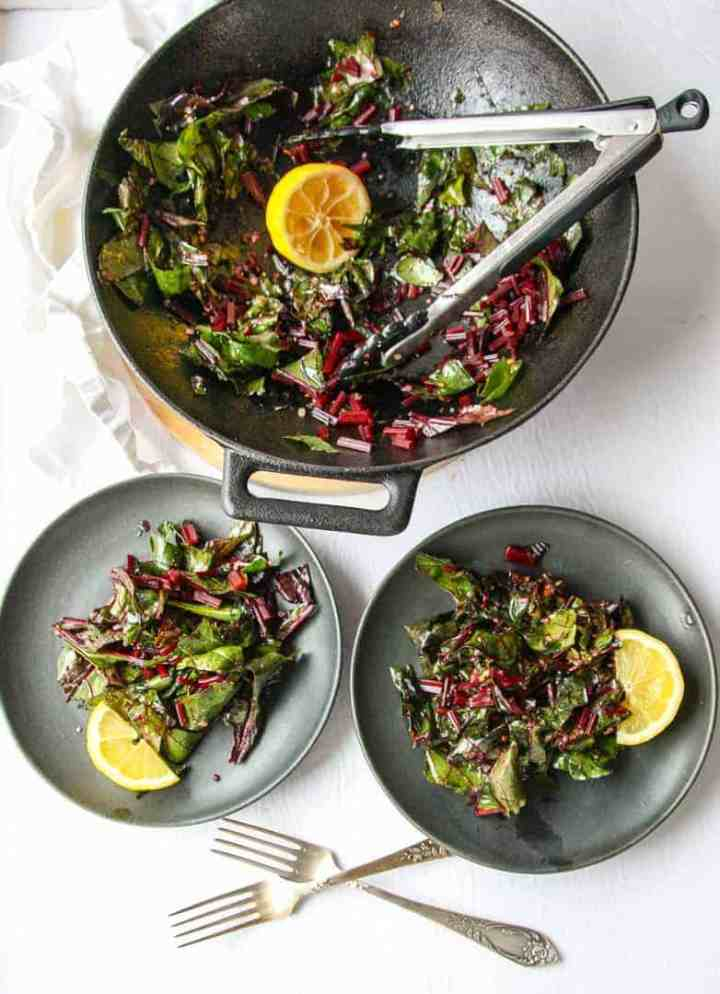 Sautéed Beet Greens being served from a pan onto two plates with tongs.