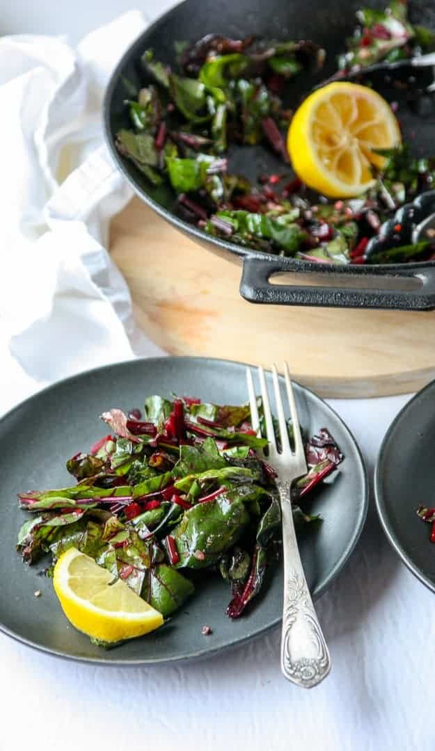 A plate of greens with a lemon wedge and a fork in front of a pan full of sauteed greens.