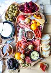An irregularly shaped wooden charcuterie board filled with meat, cheese, olives, nuts and fruit, surrounded by crackers and bread.