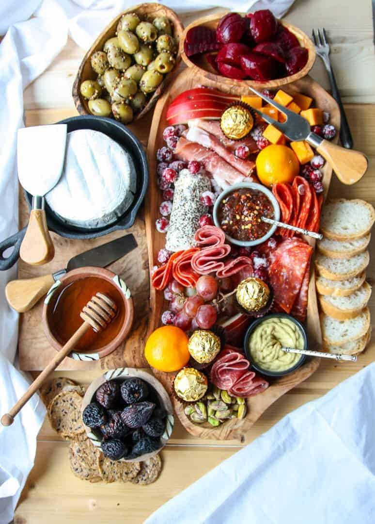 A wooden Holiday Charcuterie Board with various meats, cheeses, olives, nuts, chocolates and fruit.
