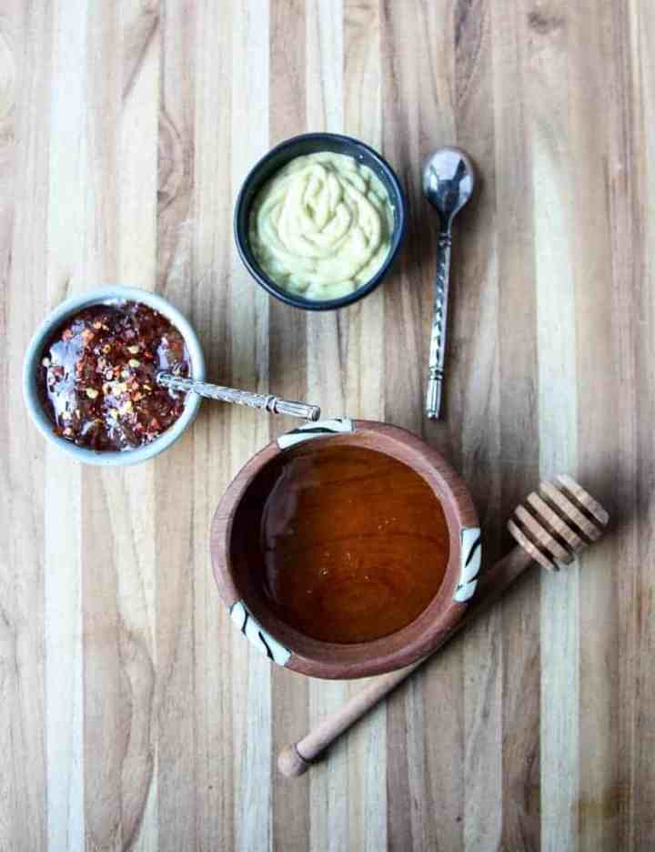 Small dishes of condiments on a wooden cutting board