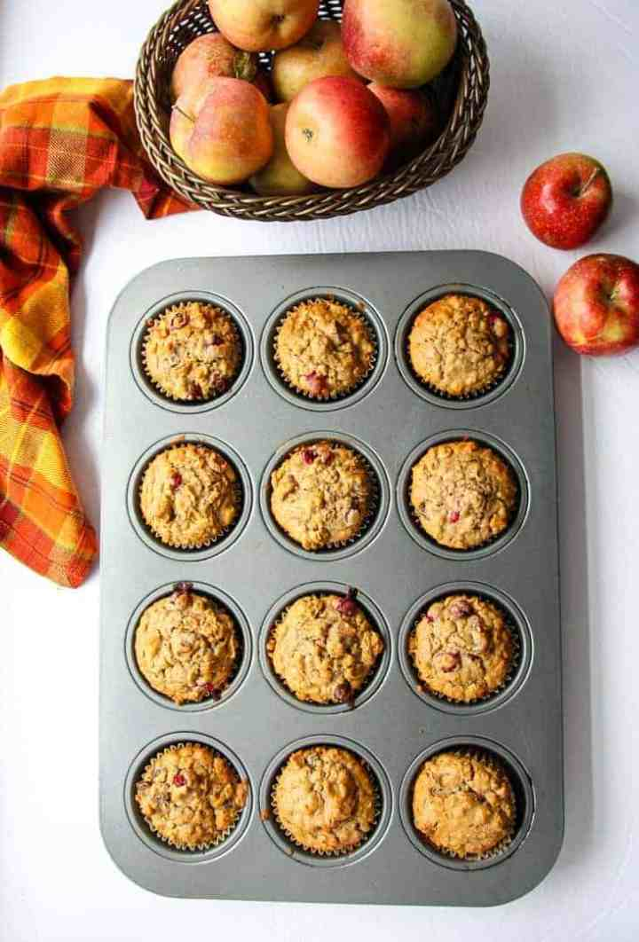 Baked muffins in a muffin tin, with a basket of apples