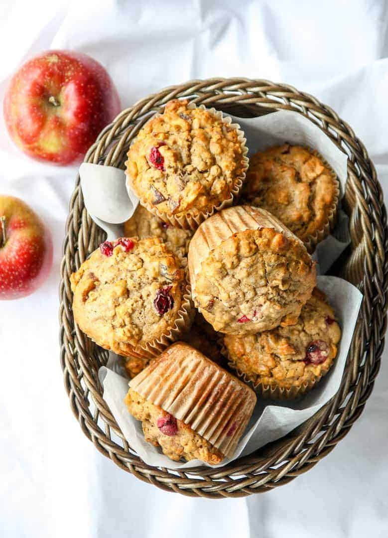 A basket filled with Apple Cranberry Muffins on a table