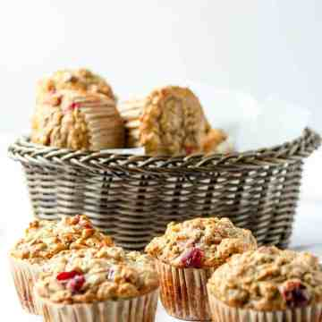 A basket of Cranberry Apple Muffins on a table