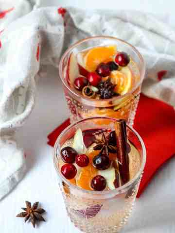 Two drinking glasses filled with wine and fruit.