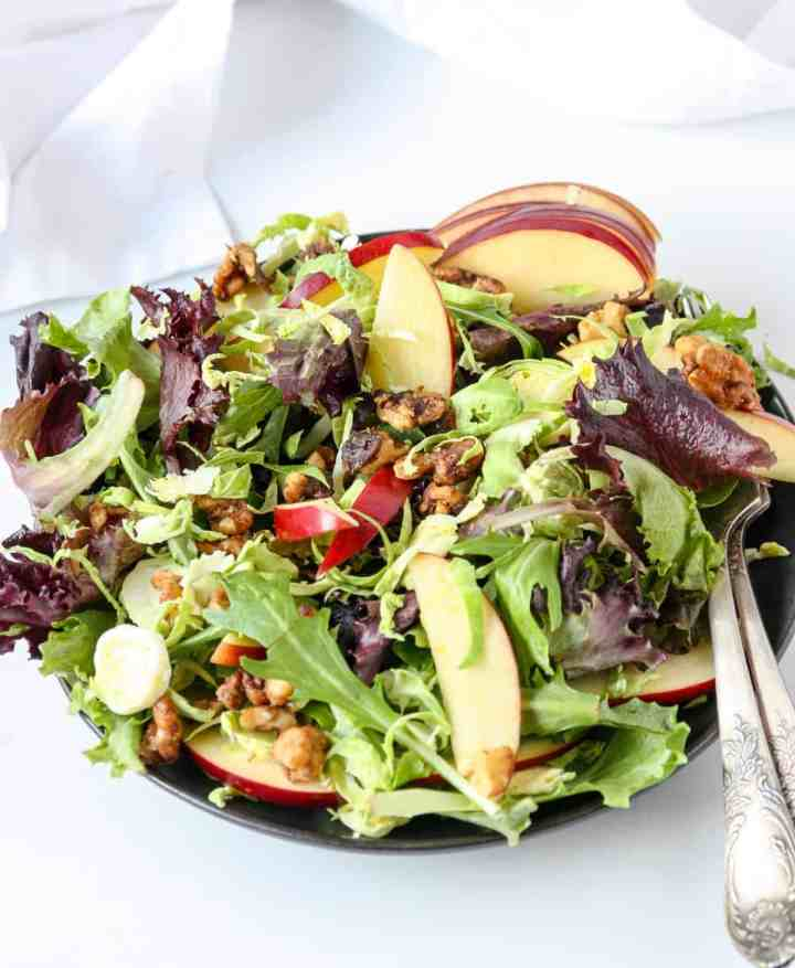 A close up of apple and brussels sprout salad on a plate.