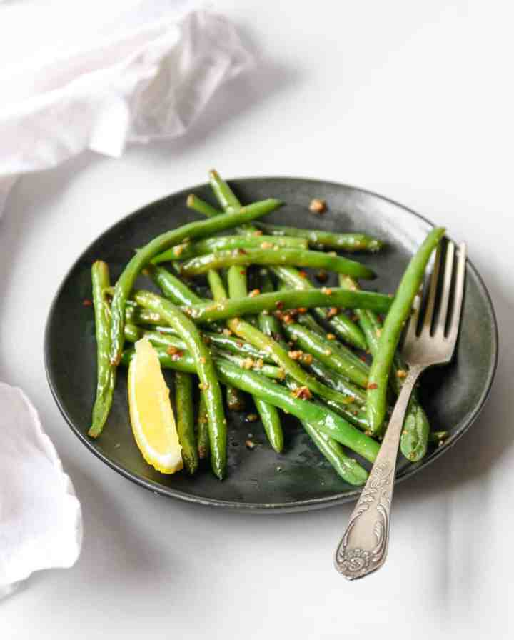 Sautéed green beans on a black plate with a silver fork.