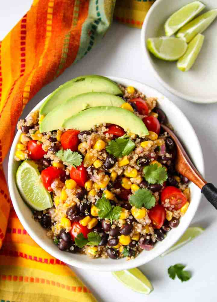 Southwestern quinoa salad in a white bowl topped with avocado slices.