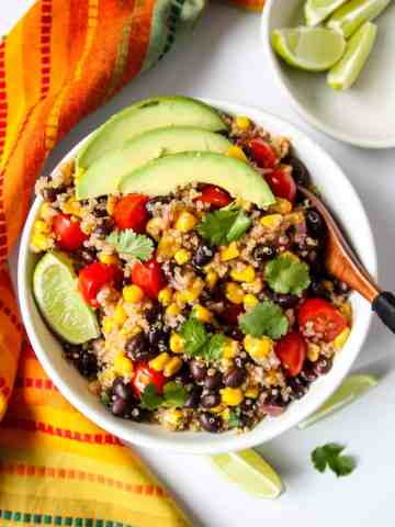 Quinoa Salad in a white bowl topped with avocado slices.