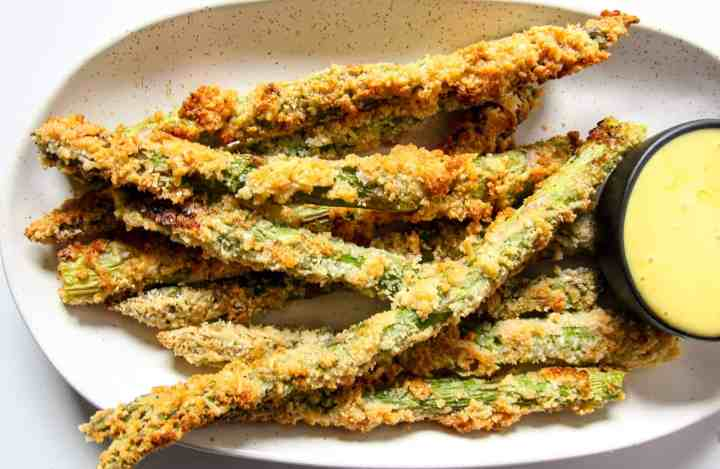 A plate of asparagus fries with a small dish of dipping sauce.