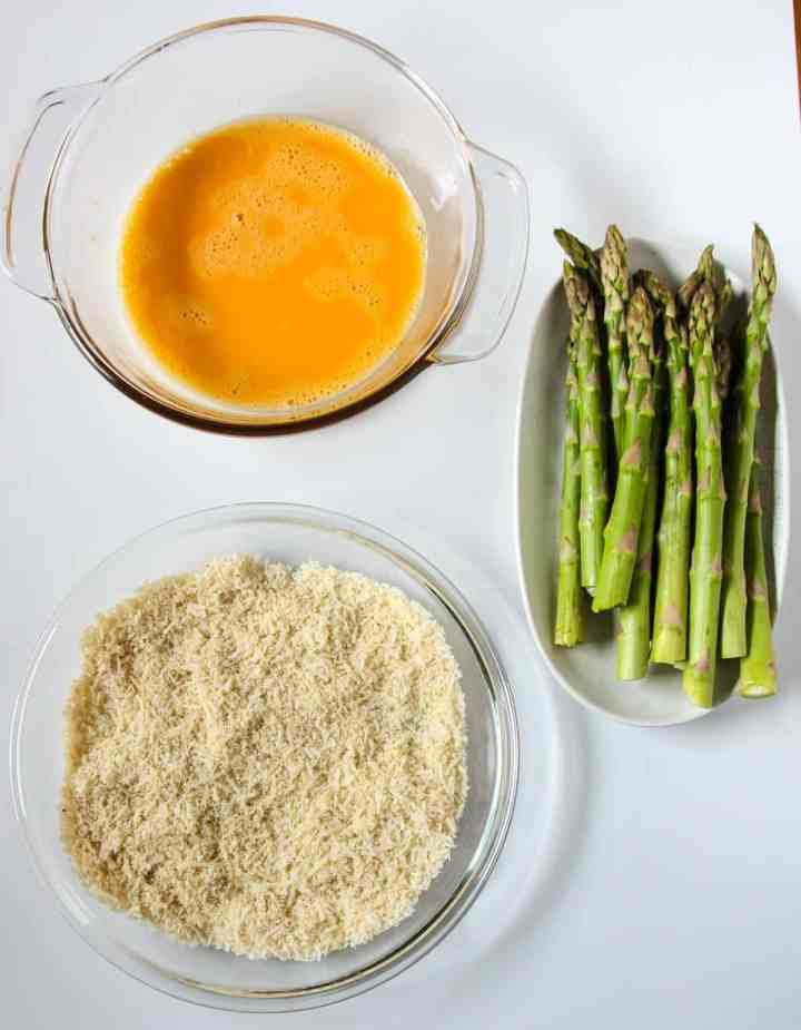 Dishes of ingredients ready for breading asparagus.