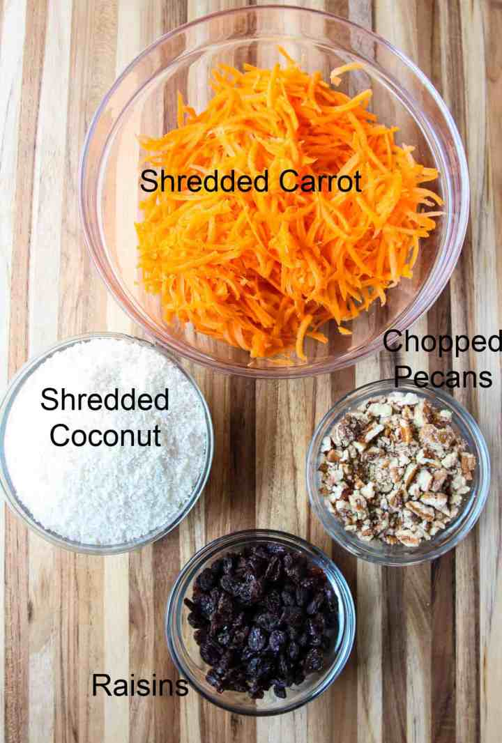 Four glass bowls containing grated carrot, coconut, nuts, and raisins.