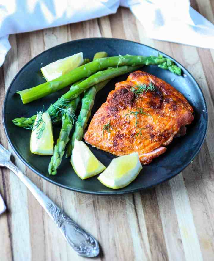 Air Fryer Salmon and asparagus on a black plate with a silver fork.