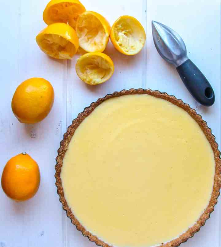 A Lemon Curd Tart on a table beside two lemons.
