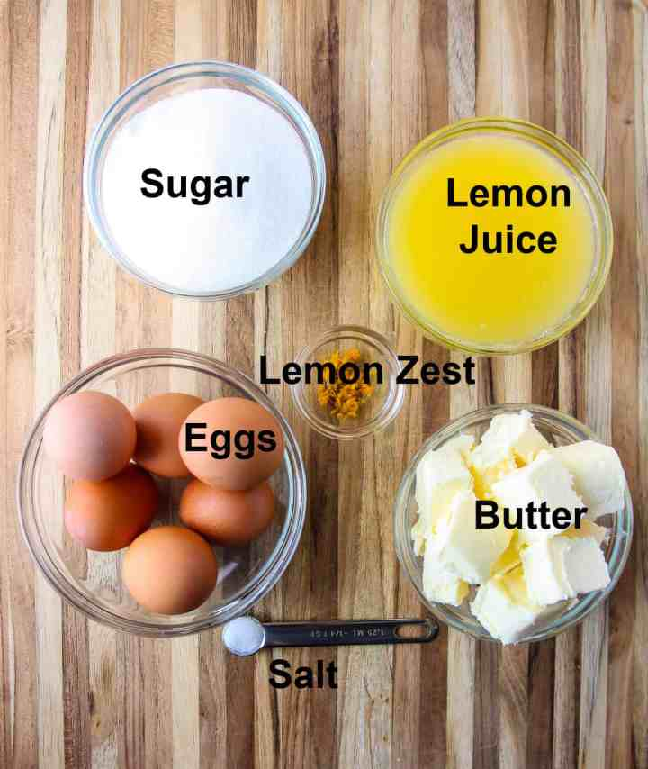Ingredients to make meyer lemon curd filling in glass bowls on a wooden board.
