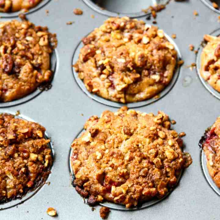 A pan of baked Strawberry Rhubarb Muffins on a wooden table.