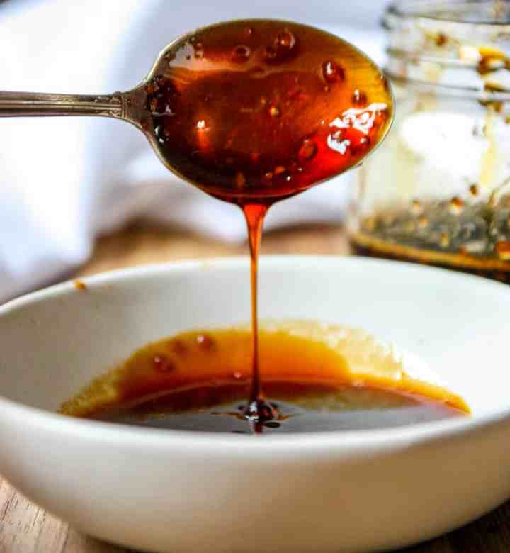 A spoon dripping with honey teriyaki sauce being held aloft over a dish.