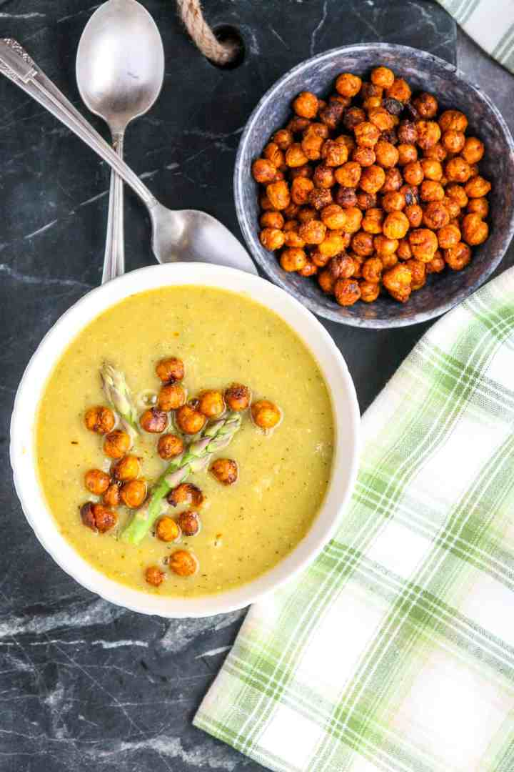 Vegan asparagus soup in a white bowl next to a small black bowl of roasted chickpeas.