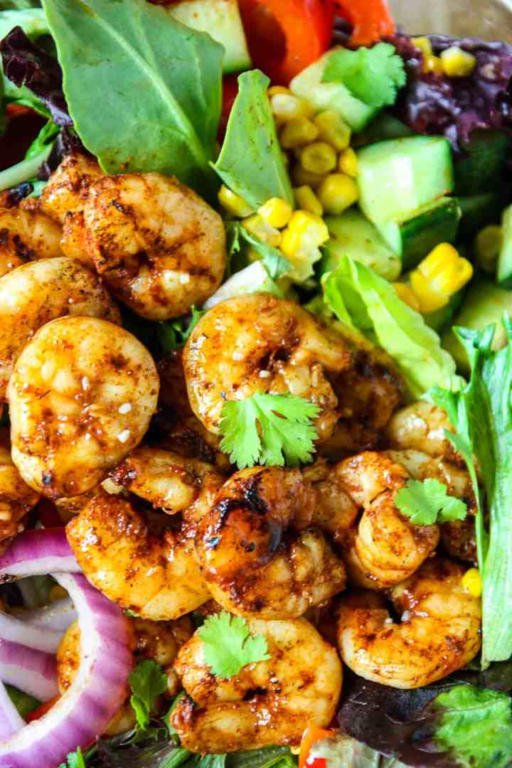 A close up of the chilli lime shrimp on a bed of salad greens.